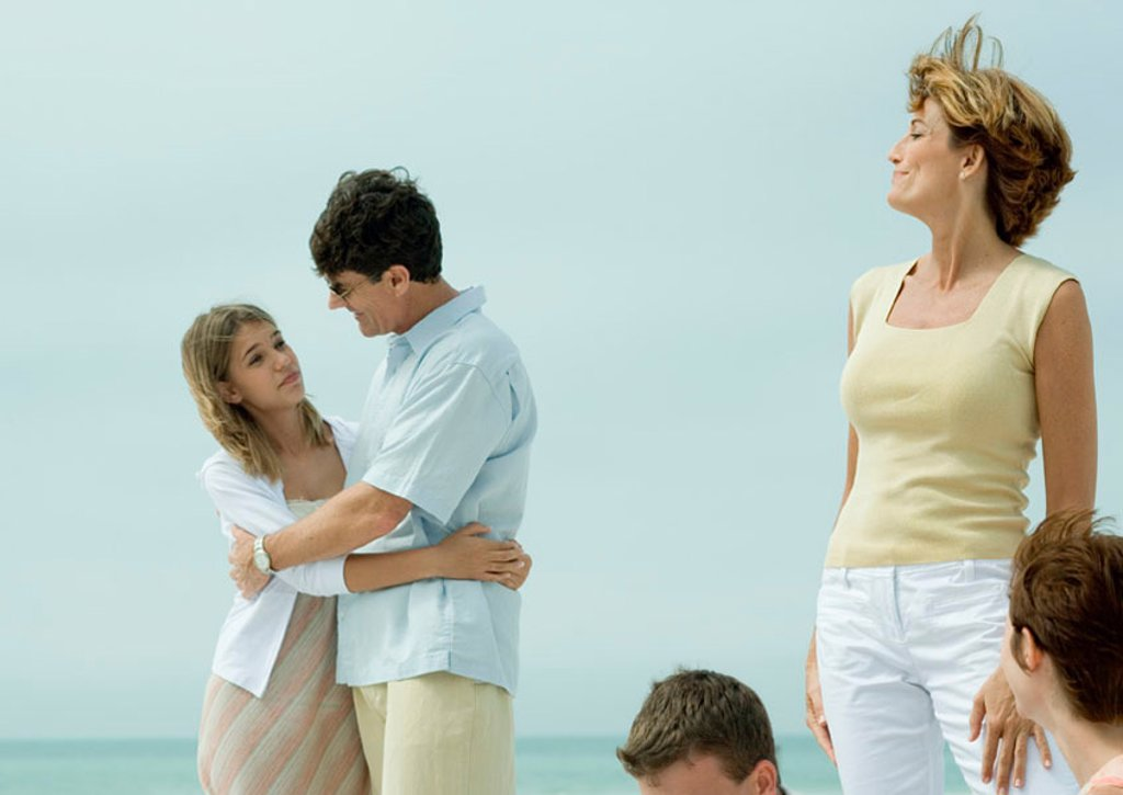 Man hugging teenage daughter while mother watches : Stock Photo