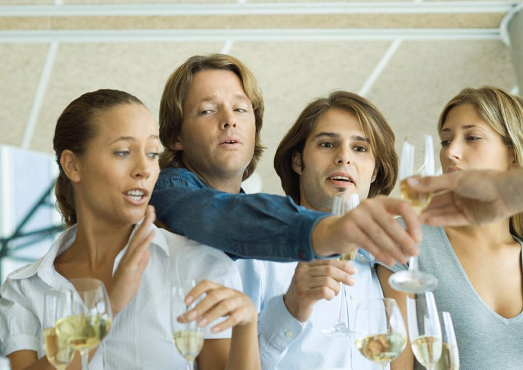 Man reaching over friends´ shoulders for glass of champagne : Stock Photo