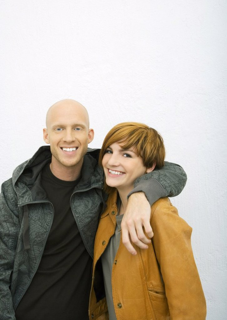 Stock Photo: 1569R-9061697 Young couple, man with arm around woman´s shoulders, both smiling at camera