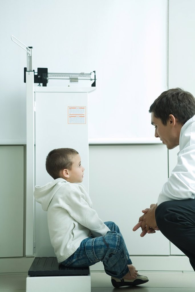 Boy sitting on scale talking to doctor in doctor´s office : Stock Photo