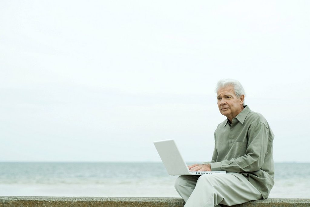 Stock Photo: 1569R-9063981 Senior man sitting near water´s edge, using laptop