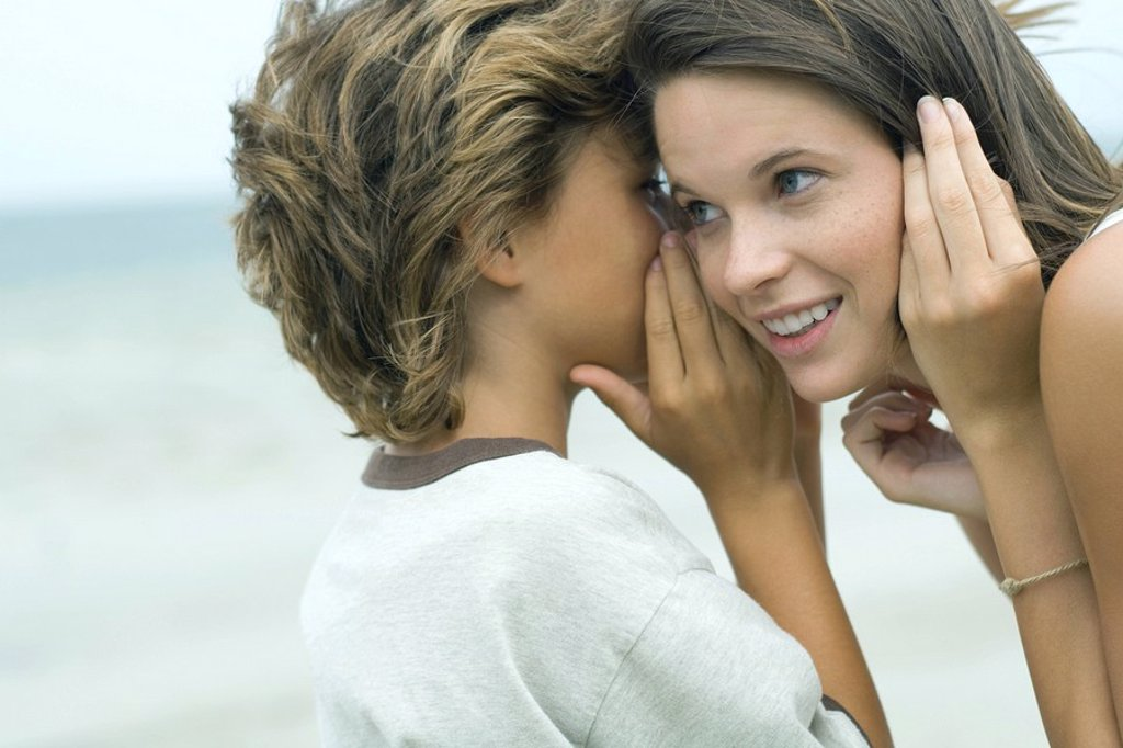 Boy whispering in teen sister´s ear, close-up : Stock Photo