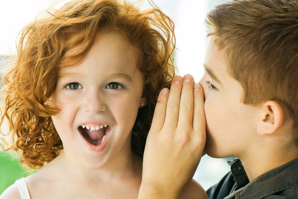 Boy whispering in girl´s ear, close-up : Stock Photo