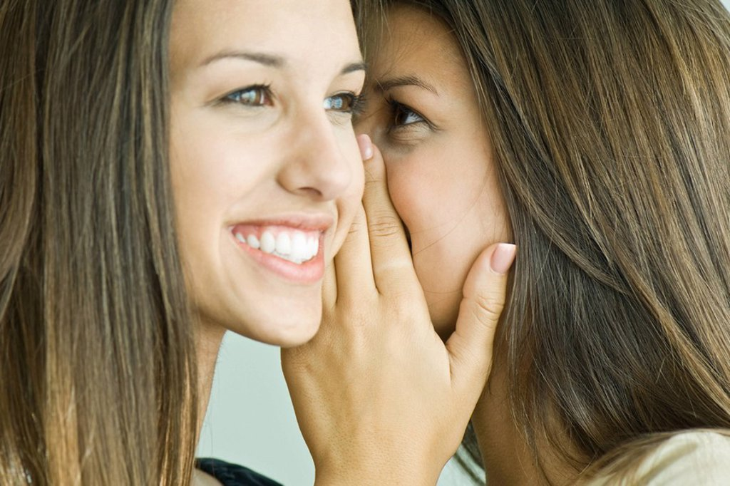 Stock Photo: 1569R-9064437 Teenage girl whispering in twin sister´s ear, close-up