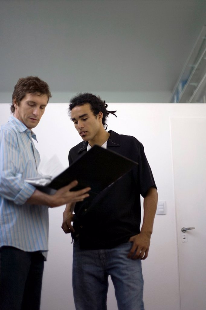 Men standing together looking over contents of binder : Stock Photo
