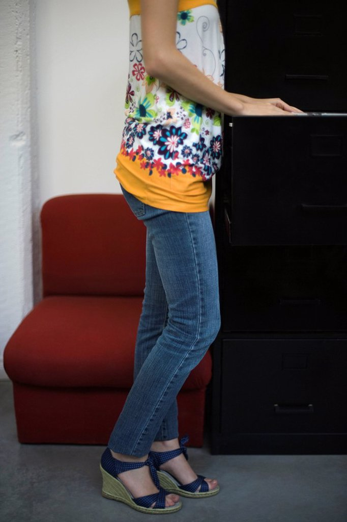 Stock Photo: 1569R-9064721 Casually dressed woman looking through filing cabinet, cropped