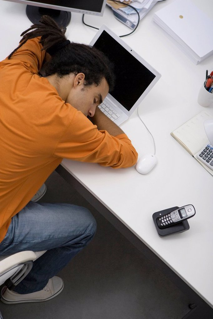 Stock Photo: 1569R-9064732 Man napping at desk, overhead view