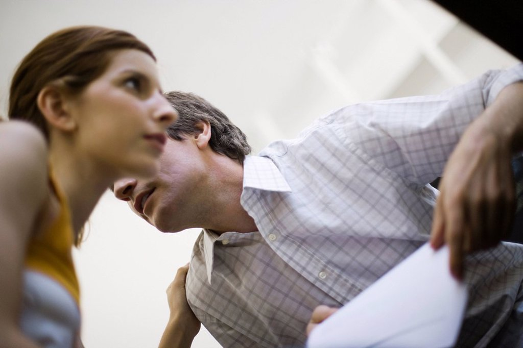 Colleagues whispering, low angle view : Stock Photo