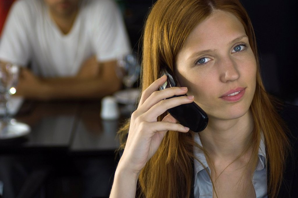 Woman holding cell phone to ear, smiling at camera : Stock Photo