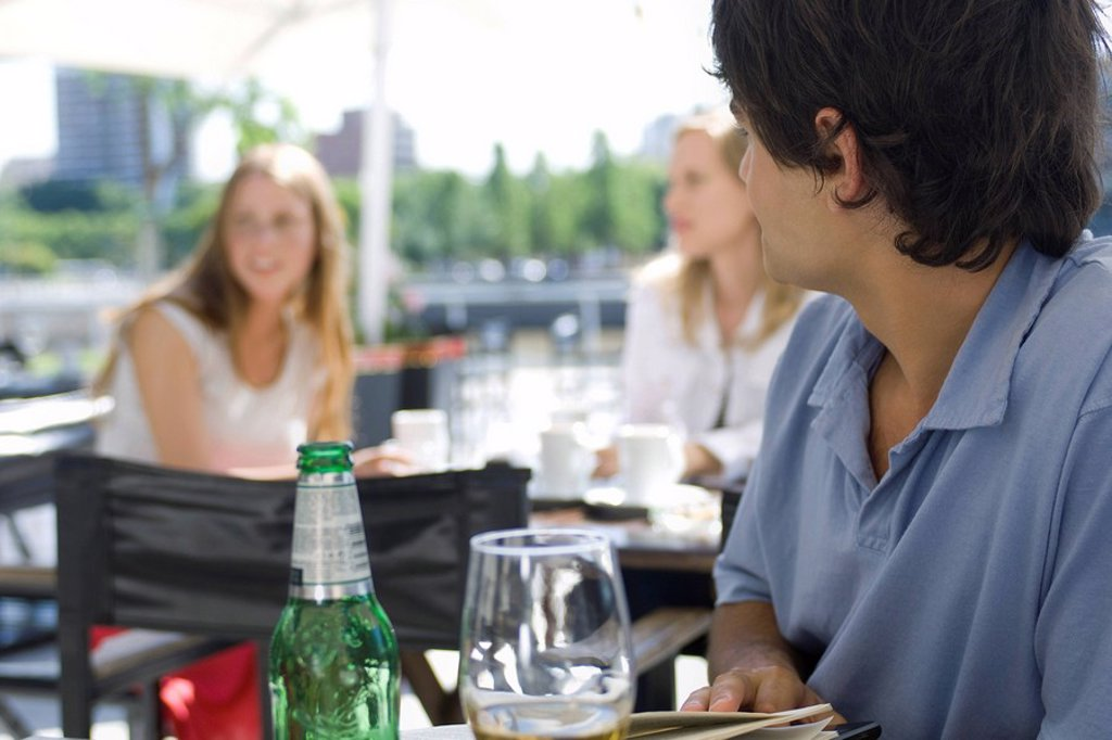 Young man sitting at outside cafe, looking over shoulder at young women sitting behind him : Stock Photo
