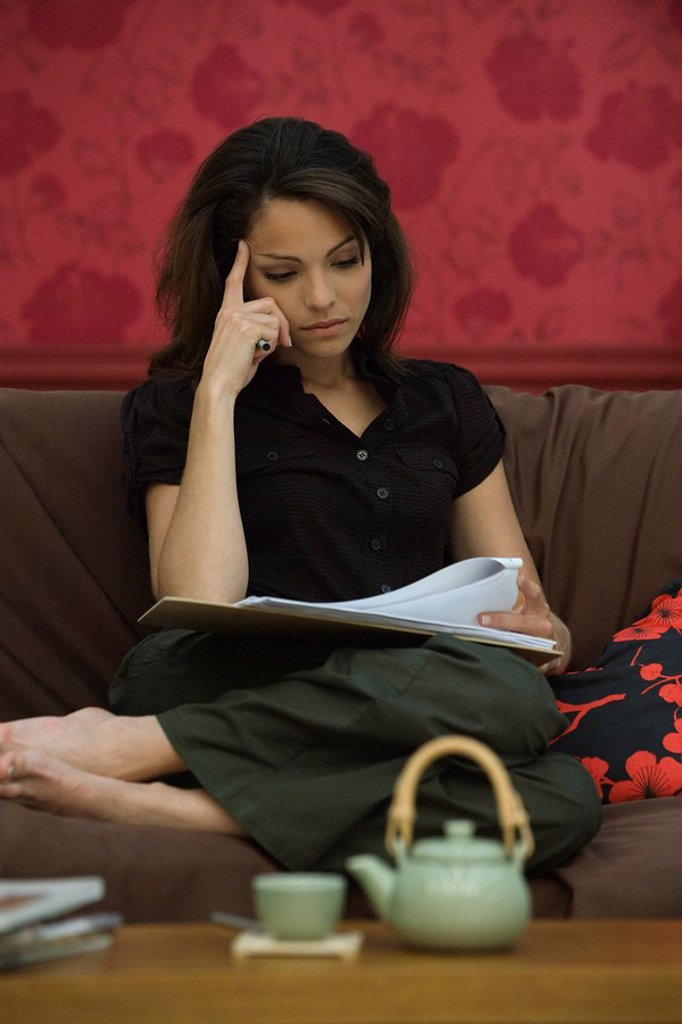 Young woman reading document on sofa : Stock Photo