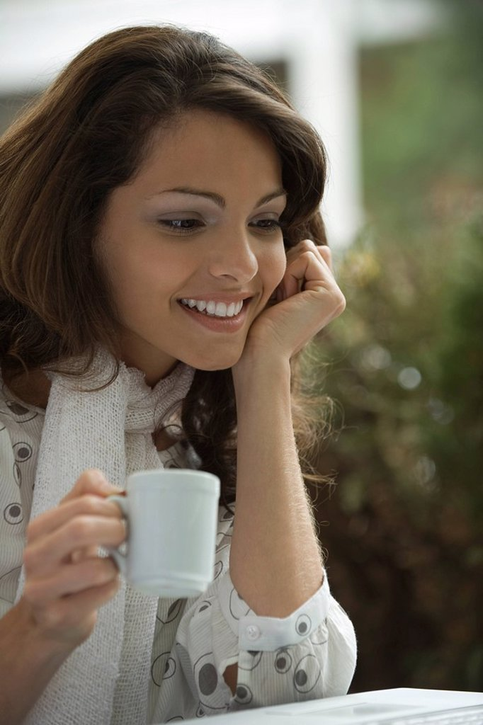 Young woman drinking coffee and looking at laptop computer : Stock Photo