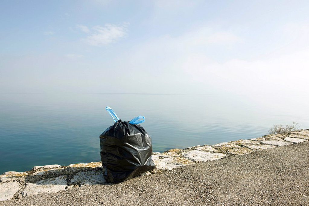 Stock Photo: 1569R-9065223 Garbage bag on ledge with sea in background