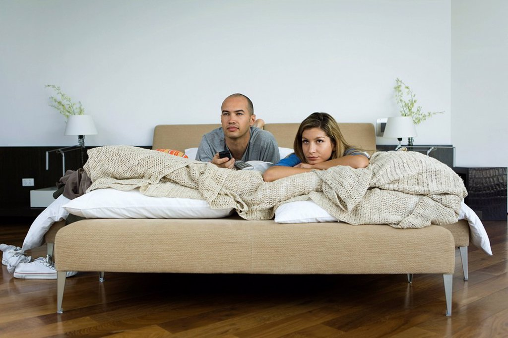 Stock Photo: 1569R-9065302 Couple lying in bed watching television