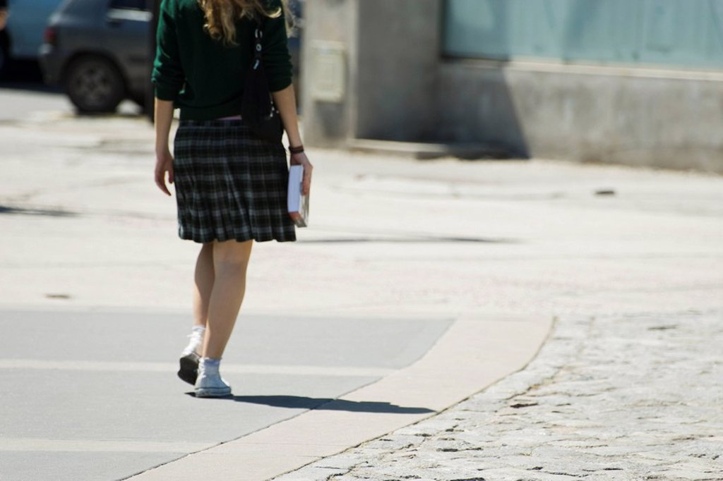 Stock Photo: 1569R-9065477 Young woman walking along sidewalk, carrying book, rear view