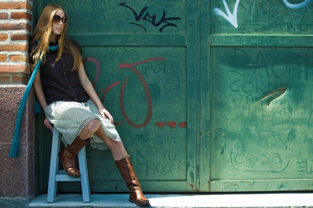 Trendy young woman sitting on stool in front of graffitied wall : Stock Photo