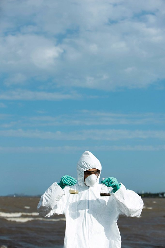 Person in protective suit holding up flasks filled with polluted water : Stock Photo