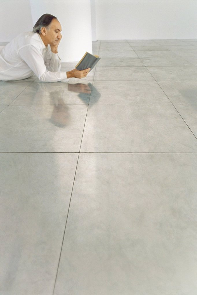 Stock Photo: 1569R-9065590 Senior man lying on stomach on tiled floor reading book