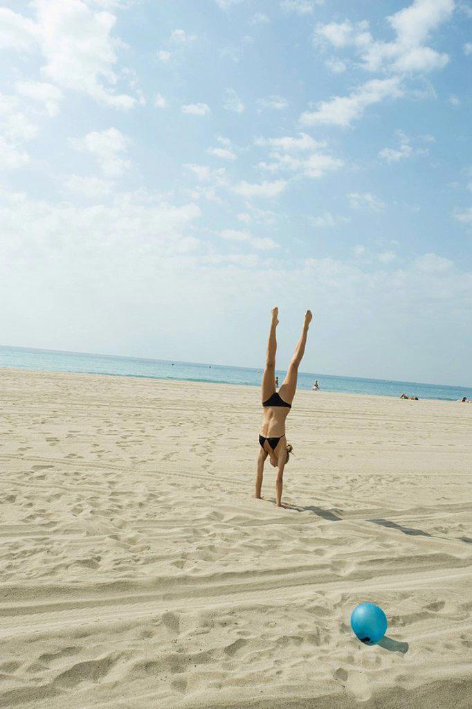 Teen girl doing handstand on beach : Stock Photo