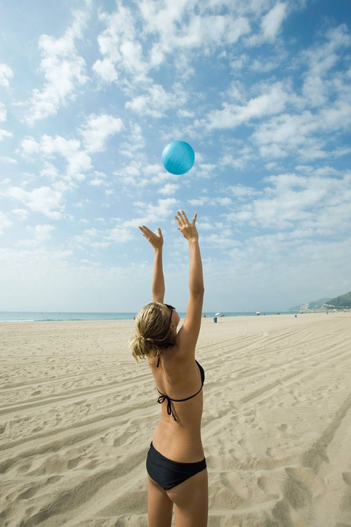 Teen girl playing beach volleyball : Stock Photo