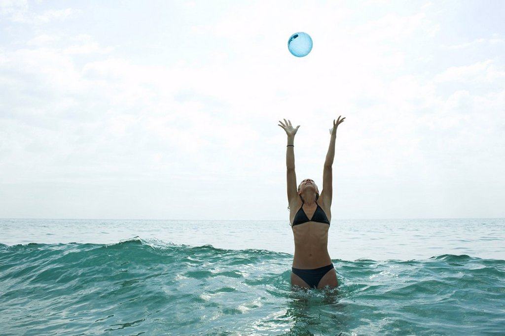 Stock Photo: 1569R-9065719 Teen girl in sea with arms raised to catch ball