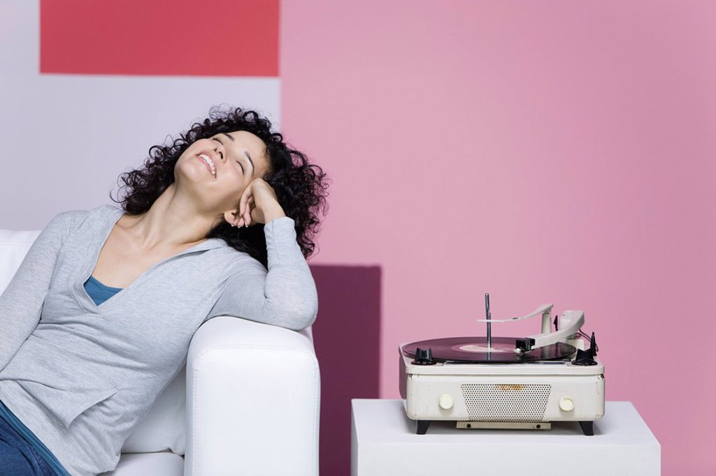 Stock Photo: 1569R-9065749 Woman enjoying music, listening to old-fashioned record player