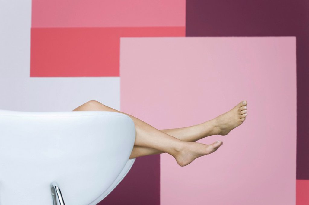 Stock Photo: 1569R-9065775 Woman reclining on armchair, cropped view of bare legs