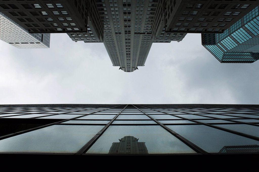 Reflection of skyscraper on glass facade of building on opposite side of street, viewed from below : Stock Photo
