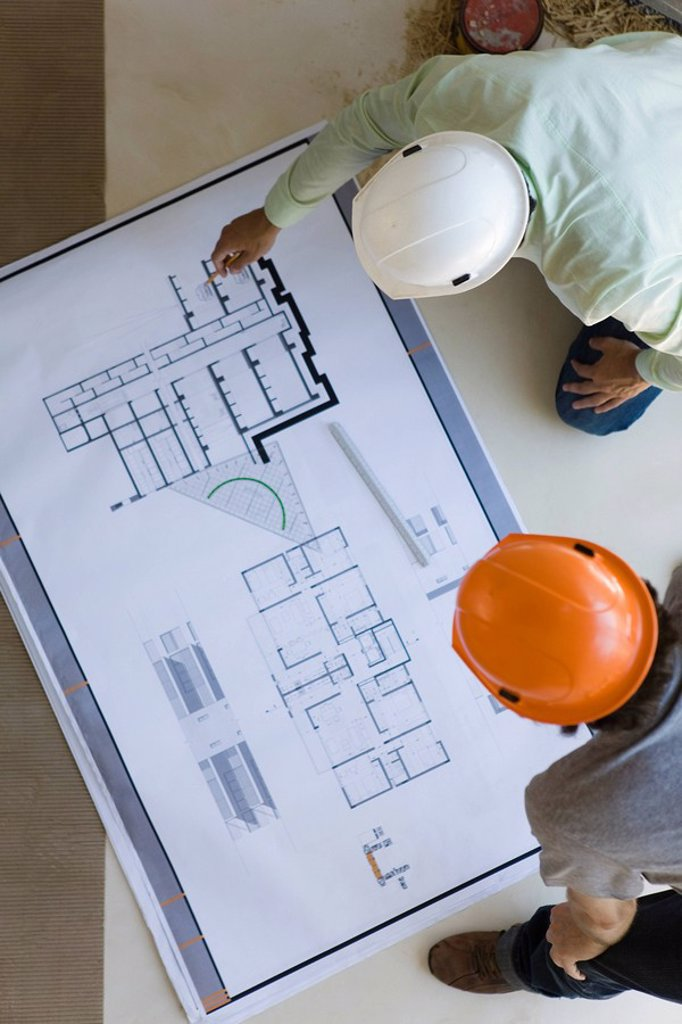 Two men crouching looking over blueprints spread out on floor : Stock Photo