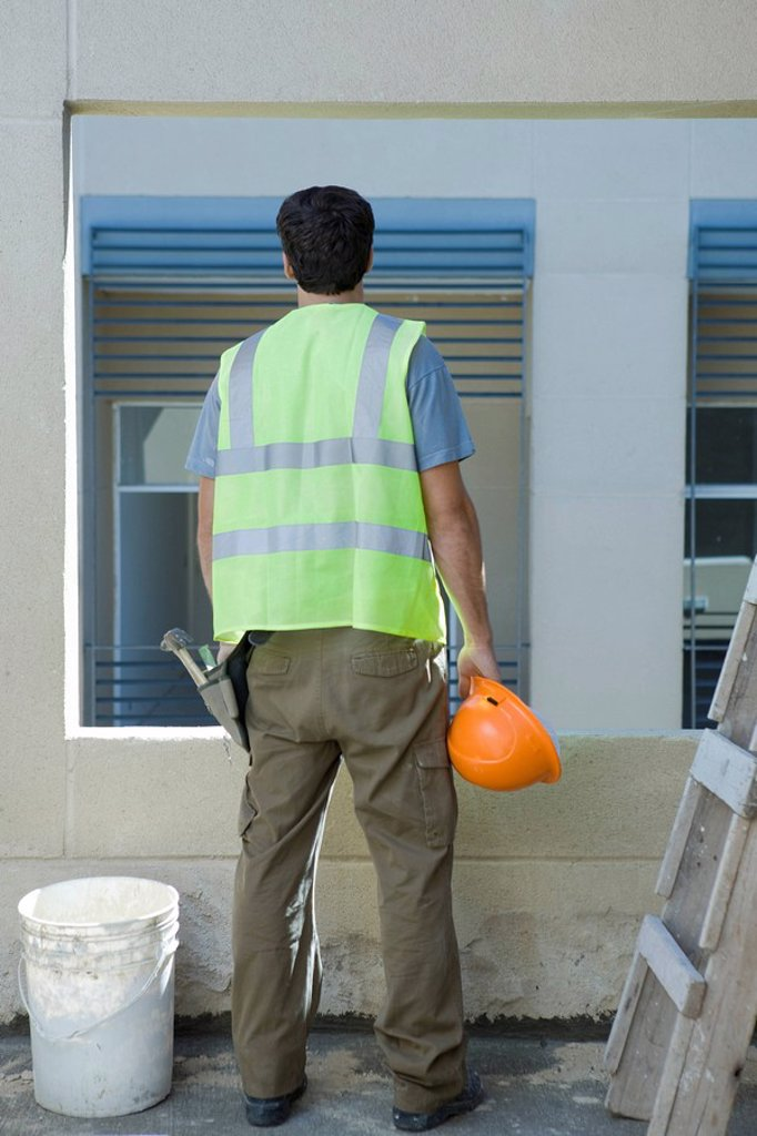 Construction worker holding hard hat looking out window : Stock Photo