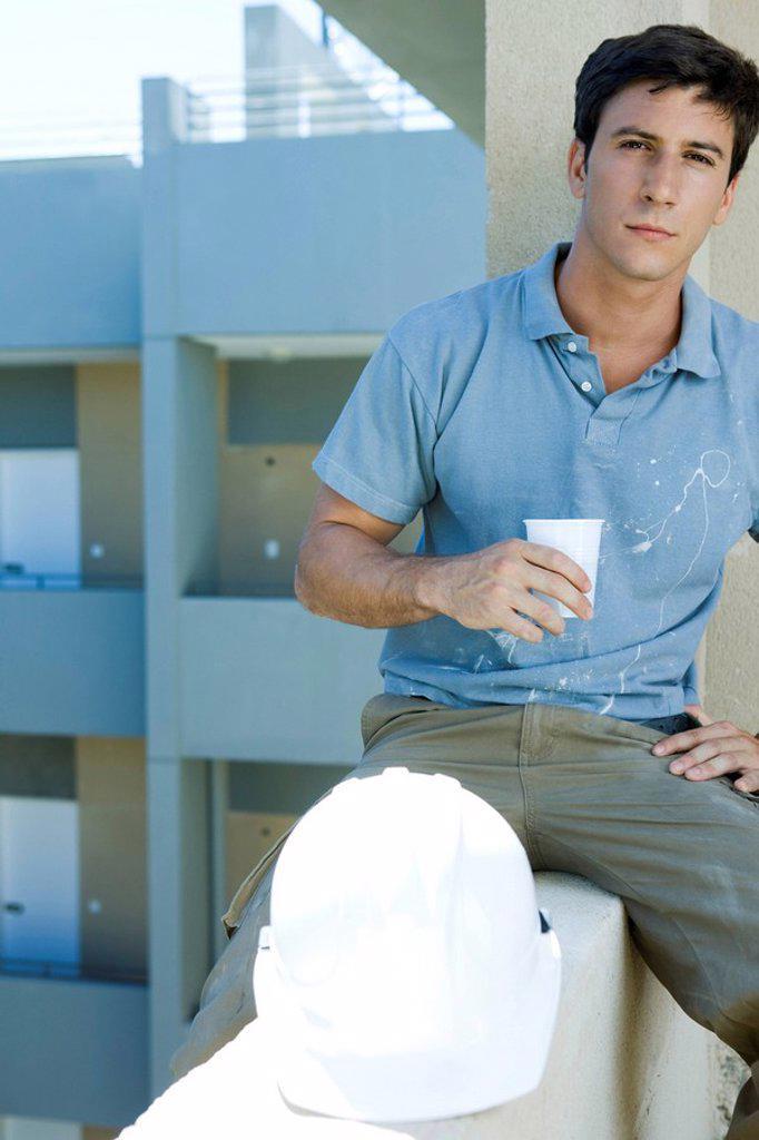 Construction worker sitting on ledge holding drink taking break : Stock Photo