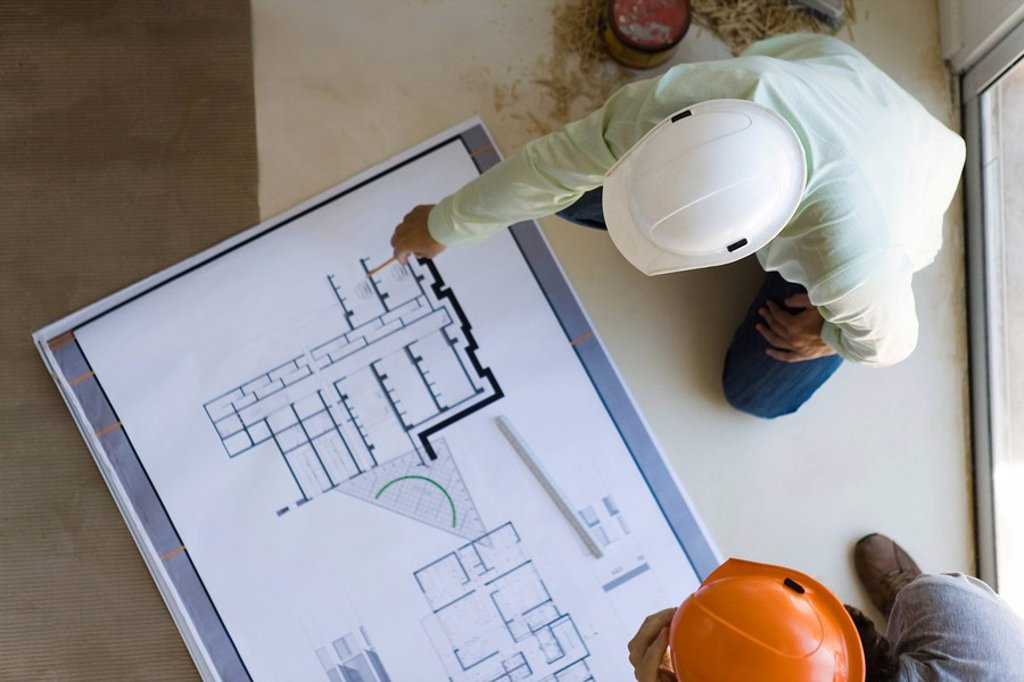Two men reviewing blueprint spread out on floor : Stock Photo
