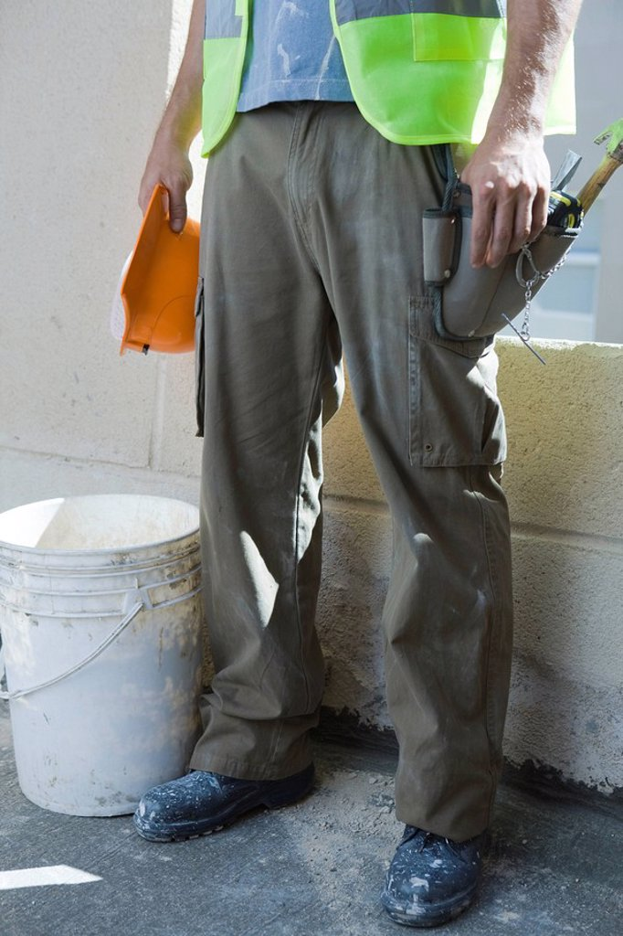 Consturction worker holding hard hat standing by bucket, low section : Stock Photo