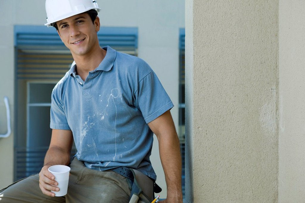 Construction worker holding disposable cup, taking break : Stock Photo