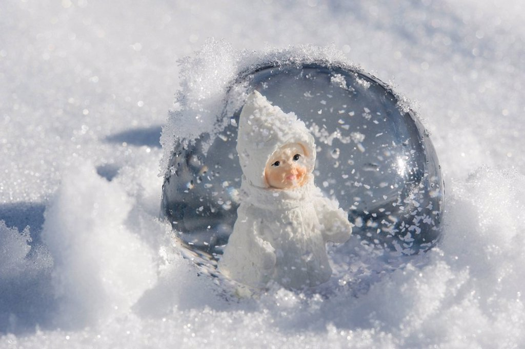 Stock Photo: 1569R-9066694 Snow globe with figurine of little girl in winter clothing sitting in snow