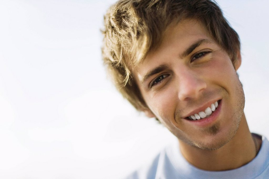 Young man smiling at camera with head tilted, portrait : Stock Photo