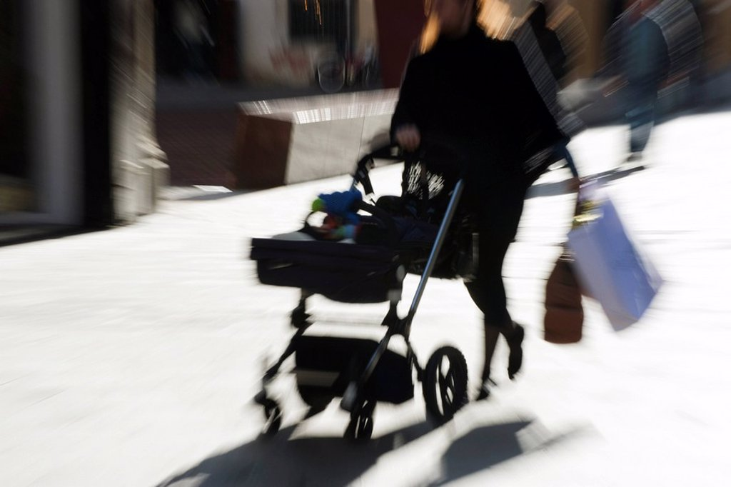 Pedestrian pushing baby carriage on sidewalk, carrying shopping bags, blurred : Stock Photo