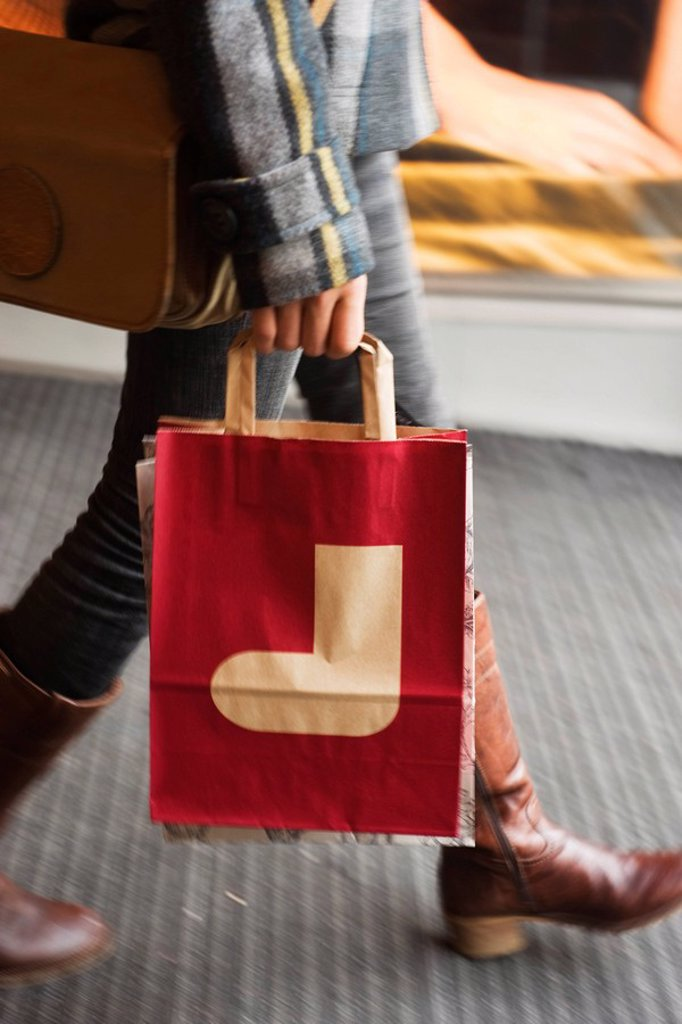 Stock Photo: 1569R-9066933 Shopper carrying shopping bag with Christmas stocking on it, cropped