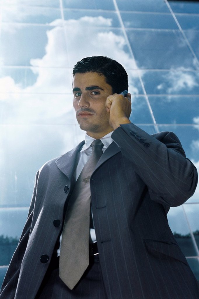 Stock Photo: 1569R-9067131 Businessman using cell phone outside office building