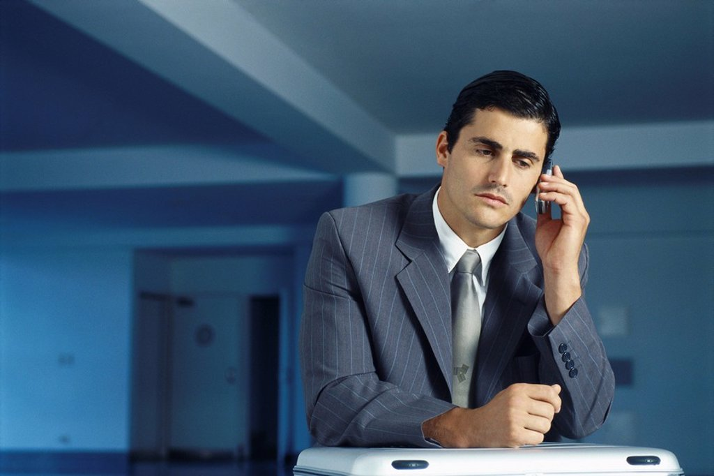 Businessman sitting with briefcase on lap in empty office using cell phone : Stock Photo
