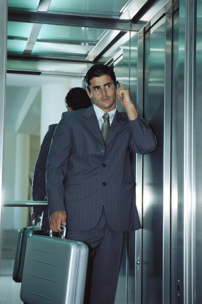 Businessman in elevator using cell phone : Stock Photo