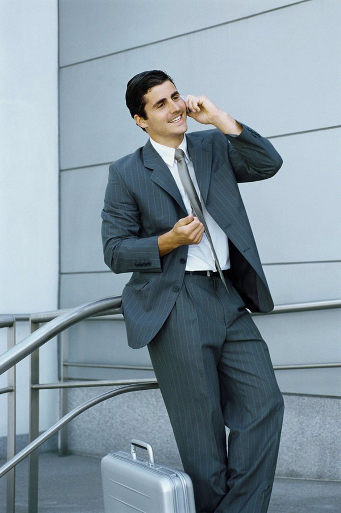 Stock Photo: 1569R-9067149 Businessman using cell phone, leaning against railing