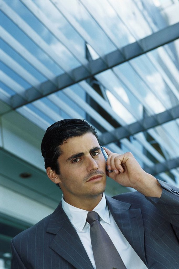 Businessman standing outside office building using cell phone : Stock Photo