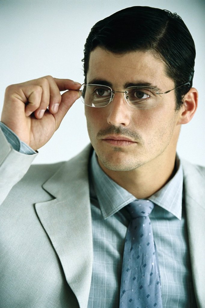 Businessman adjusting glasses, portrait : Stock Photo
