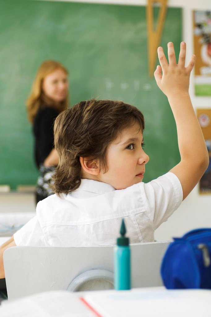 Boy raising hand in class, looking over shoulder : Stock Photo