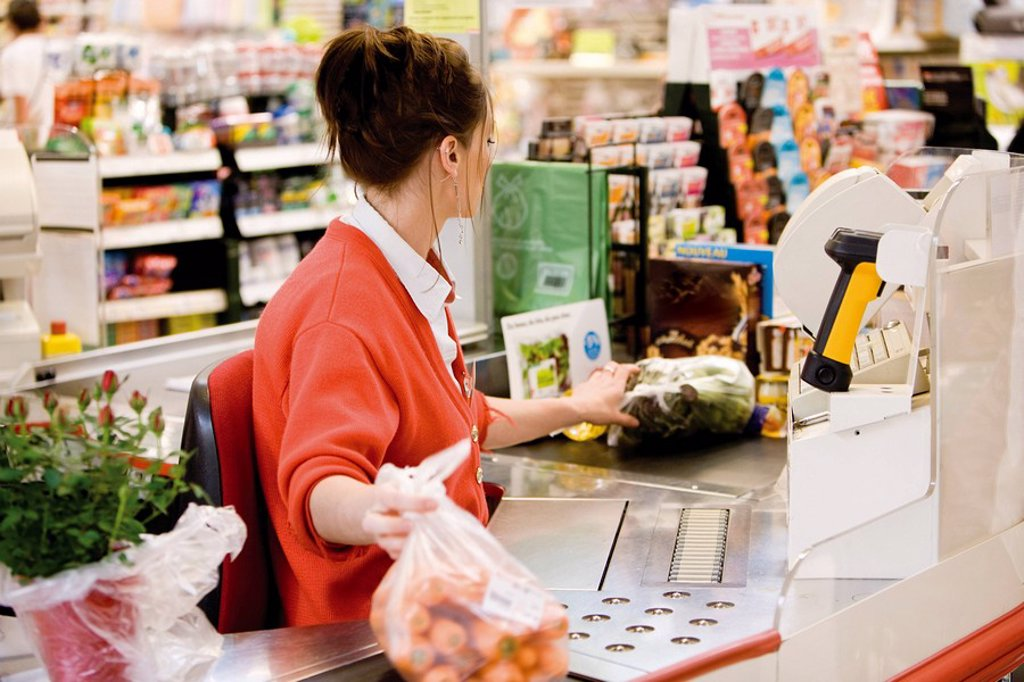 Stock Photo: 1569R-9067432 Cashier totaling grocery purchases
