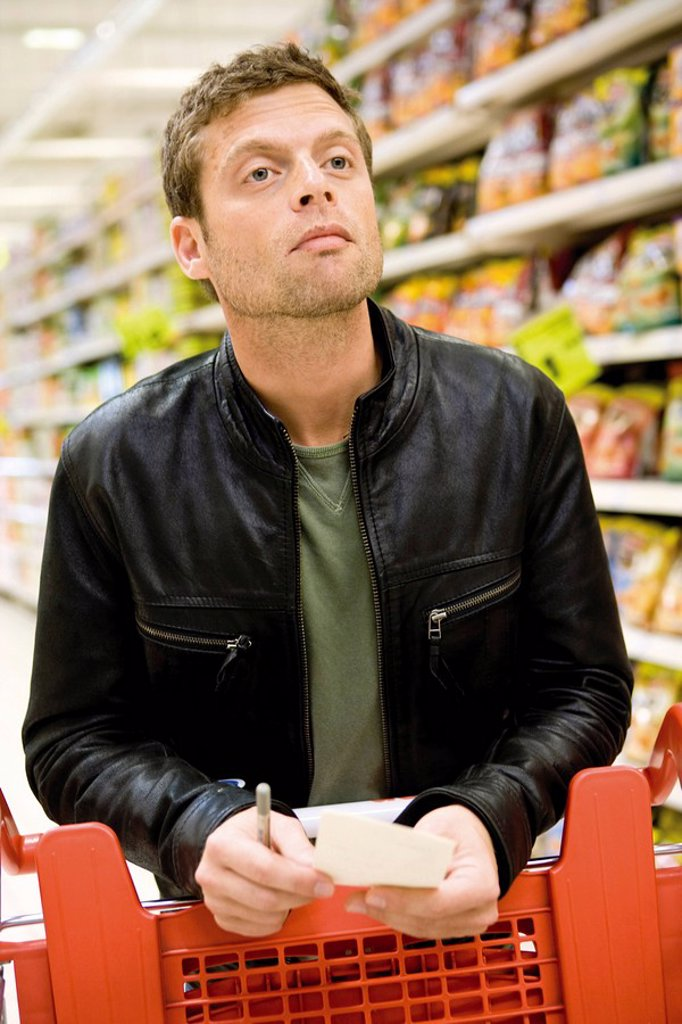 Man in supermarket with shopping list : Stock Photo