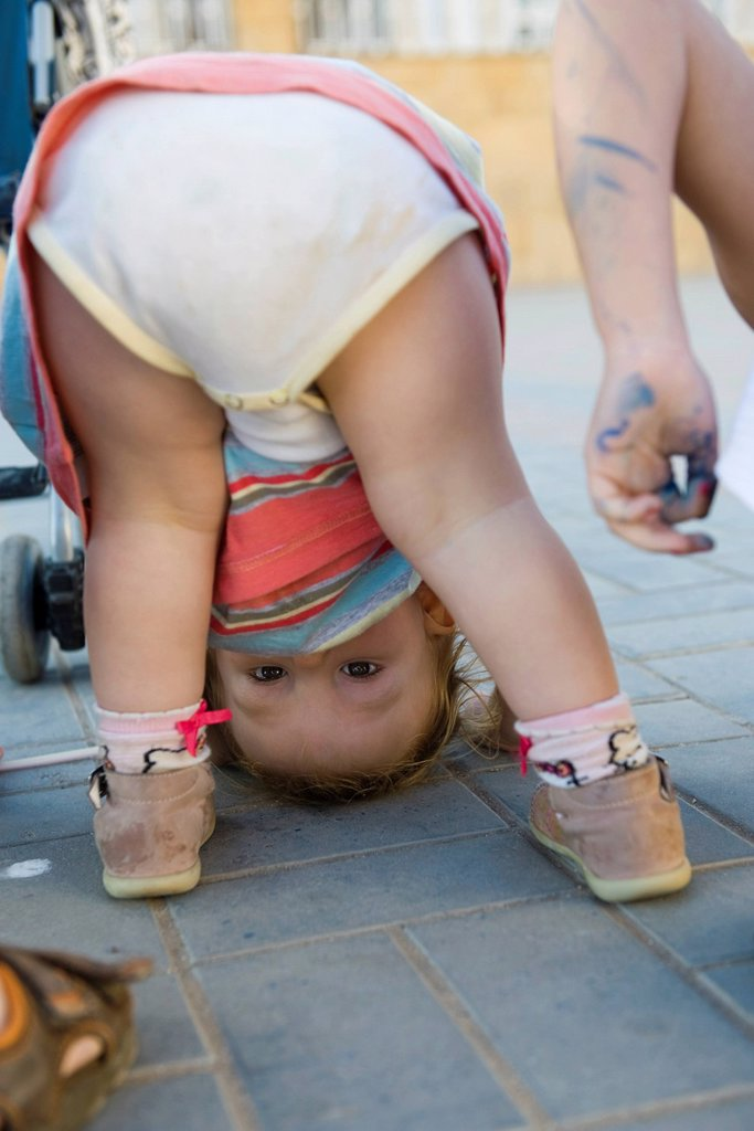 Toddler girl bending over, peeking through legs at camera : Stock Photo