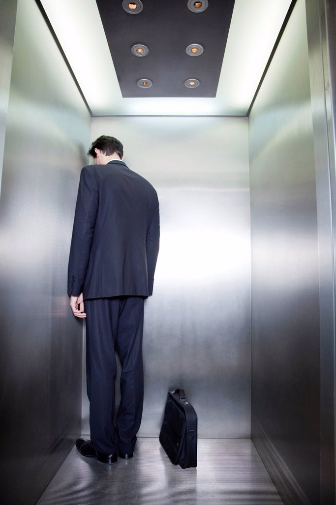 Businessman standing in corner of elevator with back to camera and head down : Stock Photo