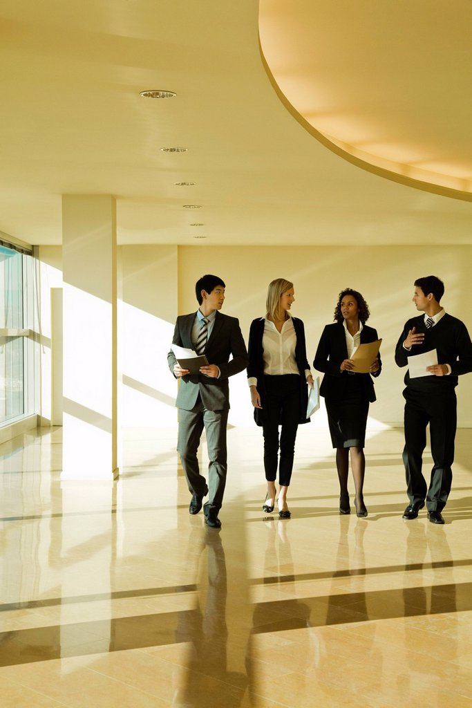 Stock Photo: 1569R-9067611 Group of executives talking as they walk together in lobby
